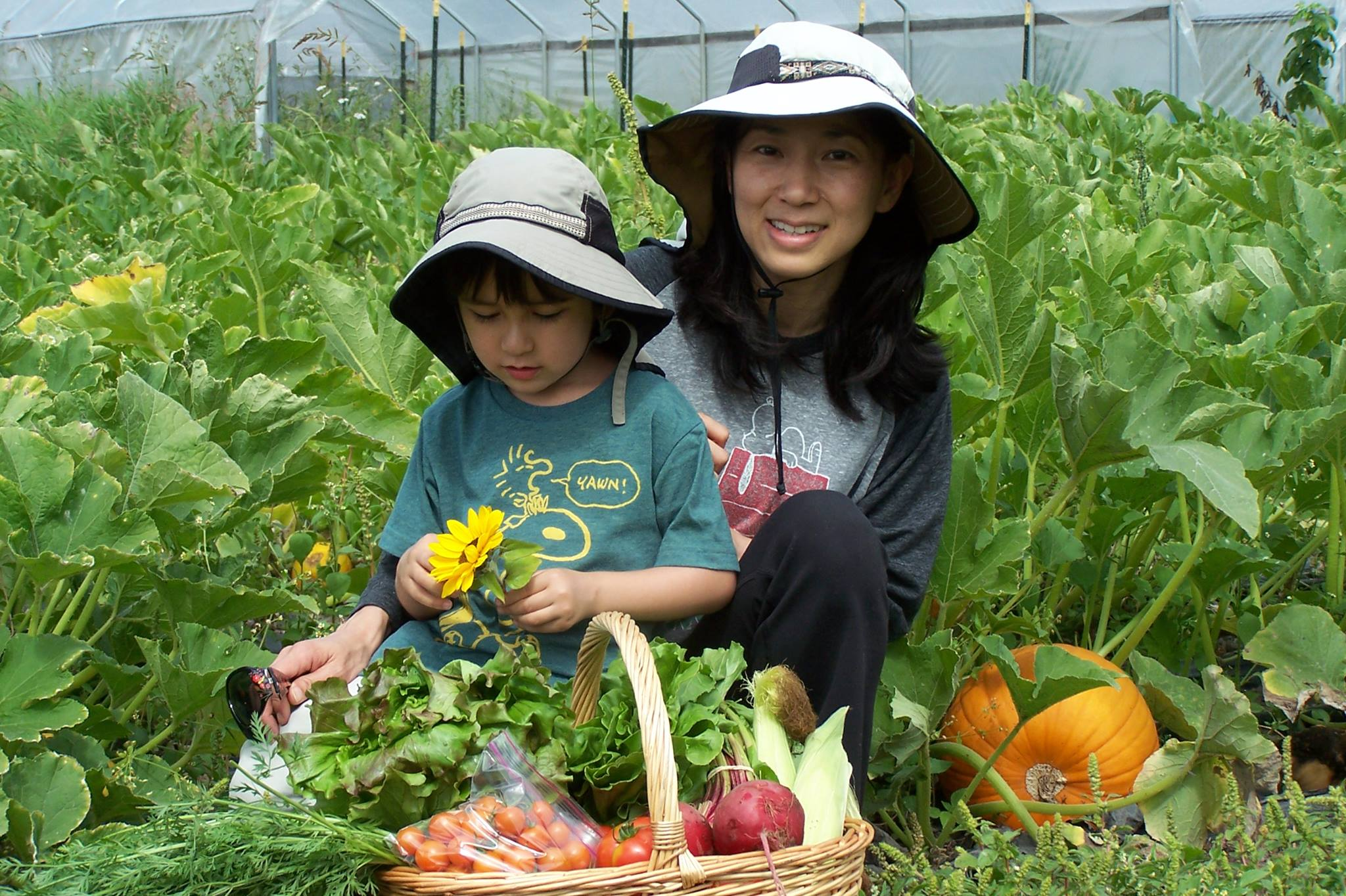 Mother and son sitting in pumkin patch with harvest basket